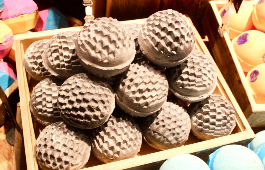 Some grey bath bombs with a prickly spot design all over them in a rectangular light wooden box, on a dark background.