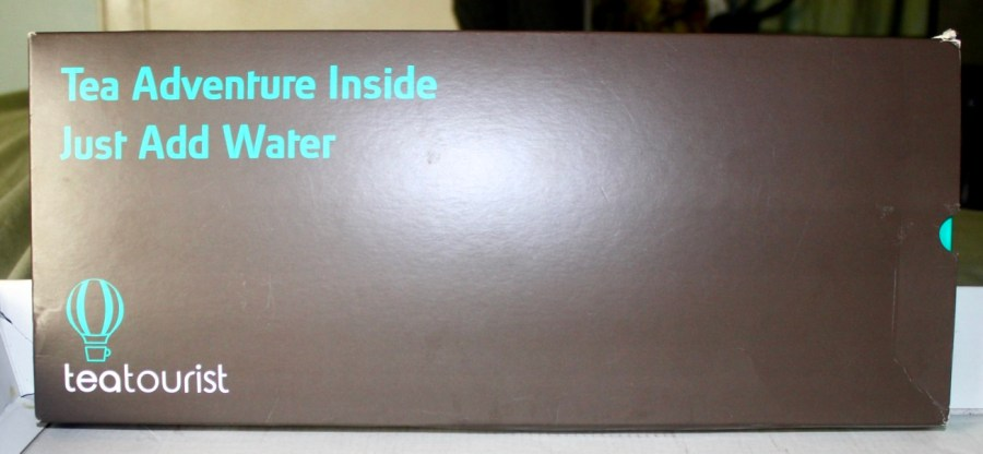 A rectangular black box that has Tea Adventure Inside Just Add Water written in Ice Blue writing and teatourist written in white writing on it, on a light background.