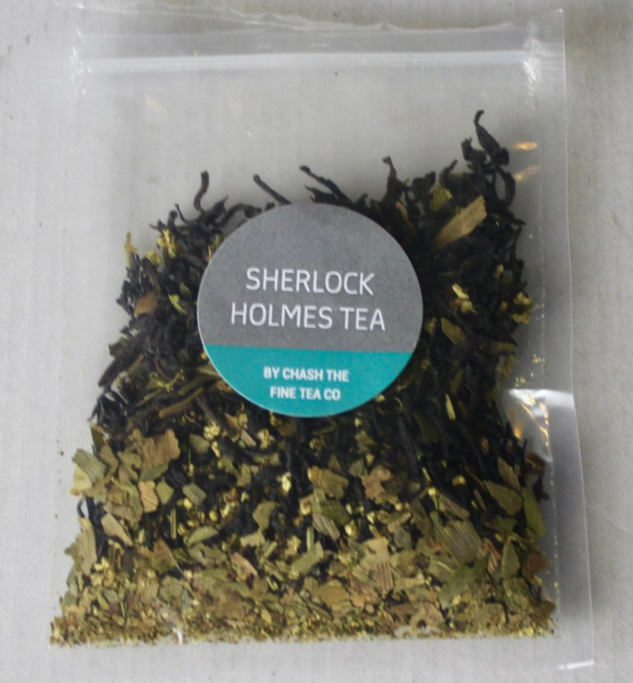 A square clear plastic bag containing some dark brown tea leaves with a light grey circular sticker that has Sherlock Holmes Tea written in medium white writing and Chash The Fine Tea Company written in smaller white writing on it, on a white background.