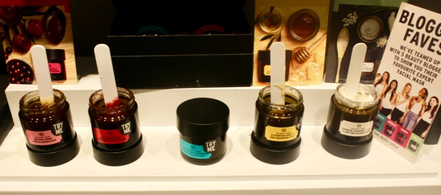 five circular black pots full of face masks and some white lolly sticks on a white shelf with a card that has blogger favourites written in bold black writing on it, on a bright background.