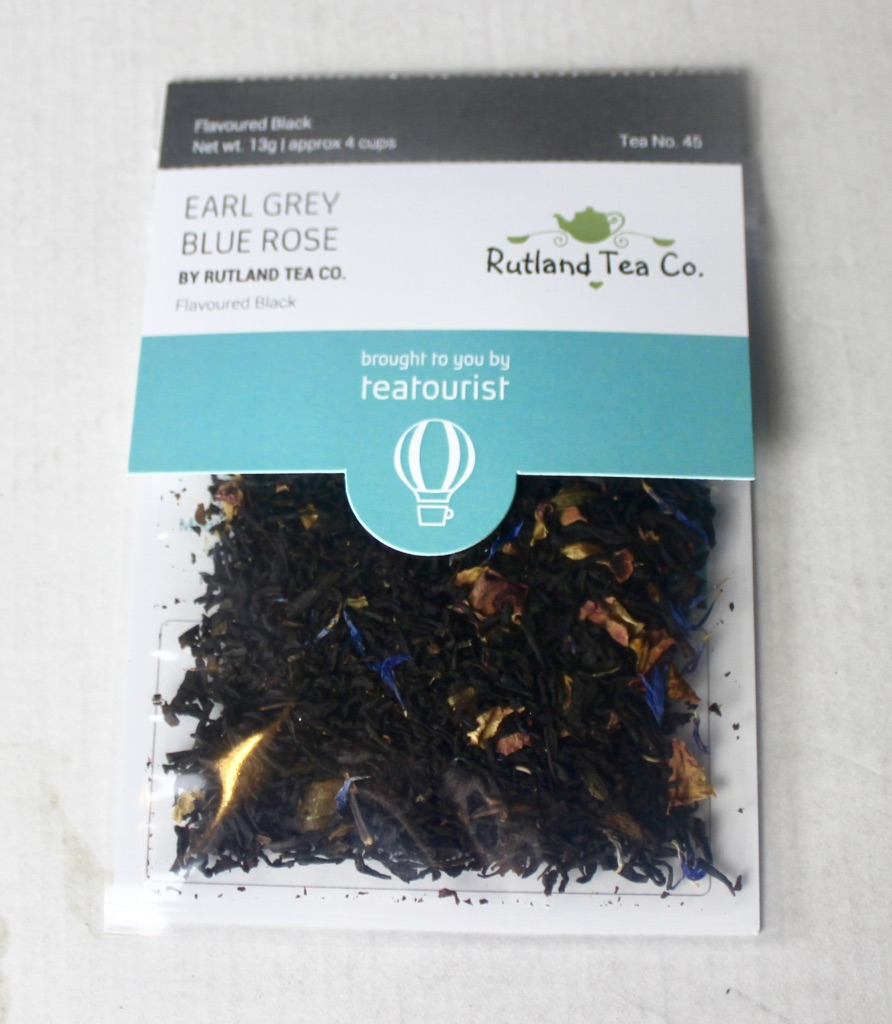 A square clear plastic bag containing some dark brown tea leaves with a cardboard label that has Earl Grey Blue Rose written in medium blue writing and Rutland Tea Company written in smaller brown writing on it, on a white background.