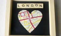 A light wooden picture frame containing a black piece of card that has a map of Oxford Street inside a heart and scrabble letters spelling London above the heart on it, on a light background.