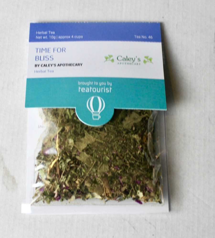 A square clear plastic bag containing some dark brown tea leaves with a cardboard label that has Time For Bliss written in light blue writing and Caley's Apothecary written in smaller light brown writing on it, on a white background.