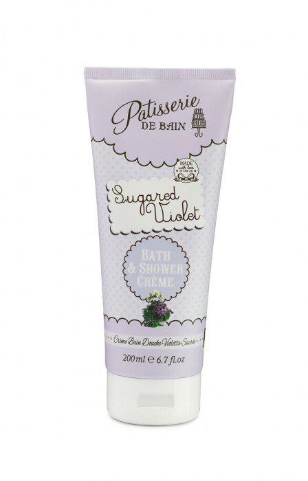 A tall white cone shaped bottle that has Patisserie De Bain and sugared violet written in pink and purple writing inside a light purple bubble and Shower Creme written in white writing inside a blue bubble, on a white background.