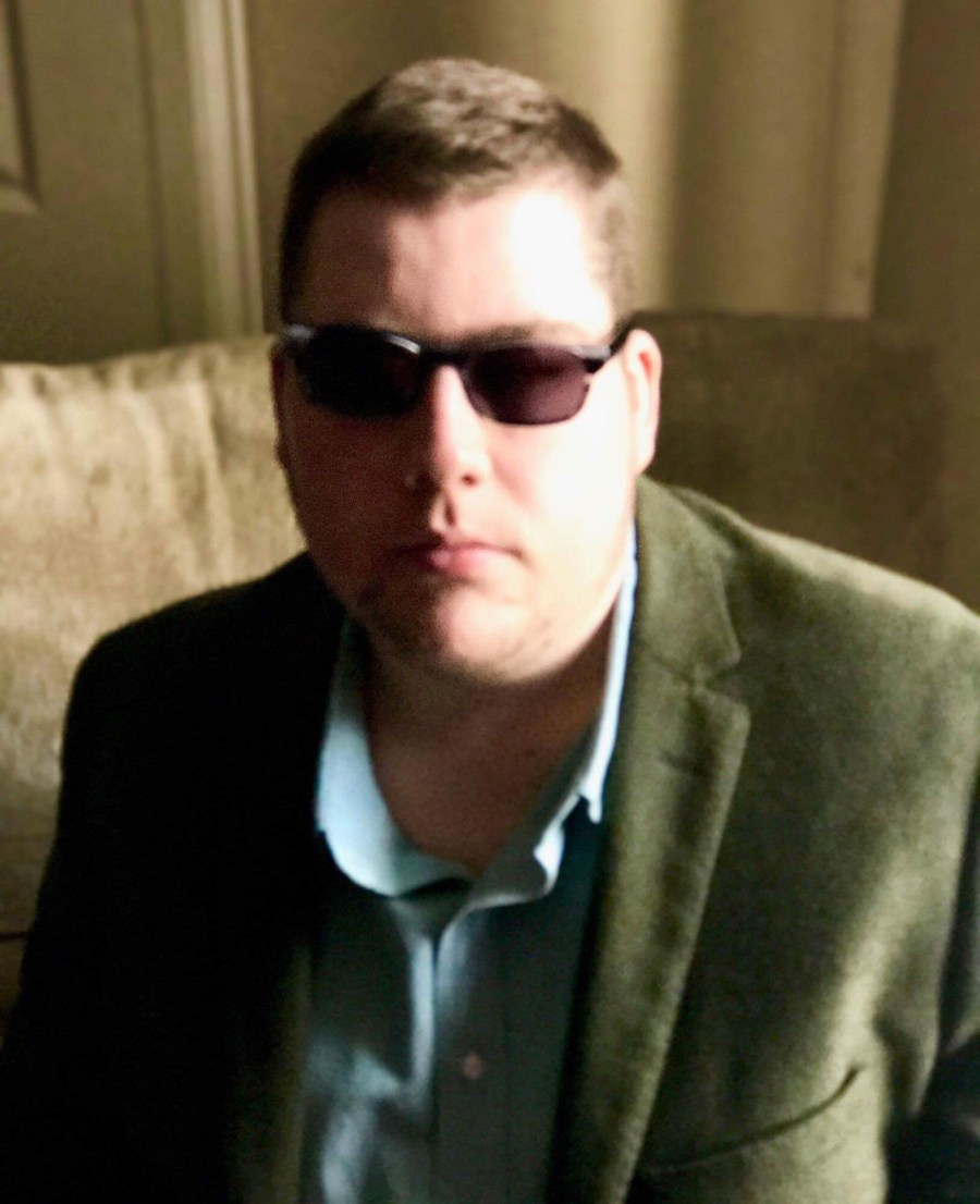 Me wearing a green blazer, a light Green shirt, and a pair of silver Aviator Sunglasses with Green lenses, on a light background.