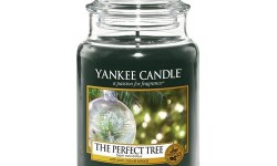 A tall glass jar full of some dark brown coloured wax with a label that has yankee candle written in white writing, The Perfect Tree written in black writing, and a picture of a tree inside a snow globe with some twinkling fairy lights on it, on a white background.