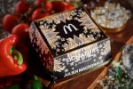 A square black Burger box that has a silver abstract design all over it, a golden McDonald's logo inside a black square, and The Signature Collection Julien Macdonald written in large Silver writing on it, on a white background.