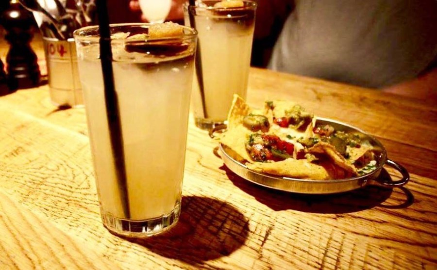 A tall glass with a black straw full of some bright yellow liquid next to a light brown bowl full of nachos on a light wooden table on a light background.