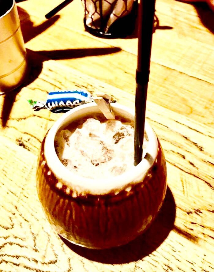 A light brown circular Coconut Shell with a black straw full of some white creamy liquid and some ice cubes next to a light blue wrapped miniature Bounty bar on a light wooden table, on a light background.