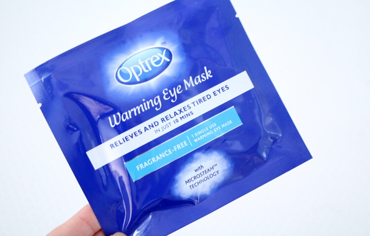 A small blue plastic pouch with a light blue oval logo that has optrex written in bold white writing and warming eye mask written in italic cursive white writing on it, on a white background.