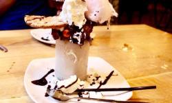 A tall milkshake glass full of some light brown liquid, some light brown chocolate fudge cake, a light brown chocolate chip cookie, some white squirty cream and some light pink candy floss on a white circular plate on a light wooden table, on a light background.