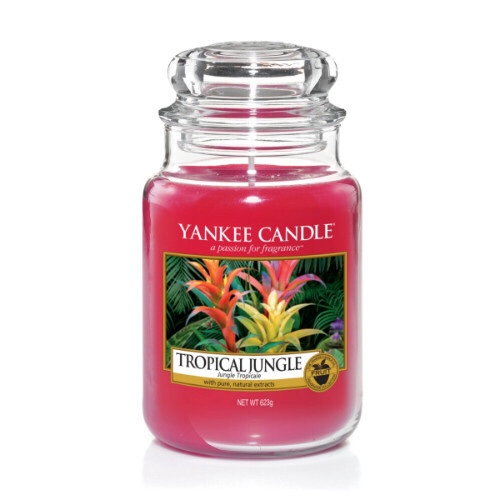 A tall glass jar full of some light Purple coloured wax with a label that has yankee candle written in black writing, Tropical Jungle written in black writing, and a picture of a bright pink jungle with some bright green leaves and bright pink and yellow flowers on it, on a bright background.