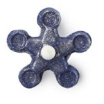 A deep blue flower shaped bubble bar that has gold glitter on it on a white background.