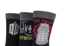 Three black socks that have a thick grey stripe, a bold silver Doctor Who logo and a dark grey heel on them, a black sock that has a silver heel, a picture of a silver Cyberman and Cyberman written in silver writing on it, and a black sock that has a picture of a gold Dalek and a gold heel on it, on a white background.