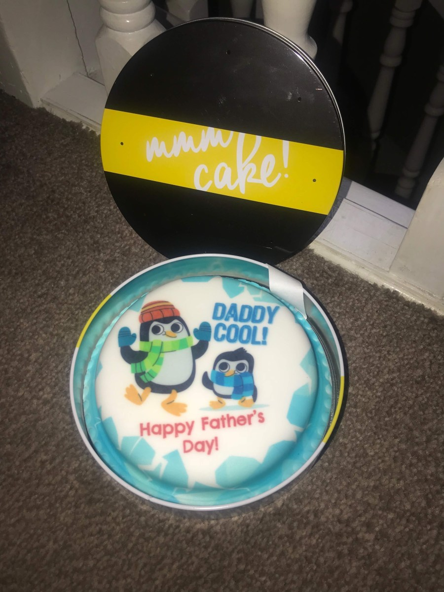 a black and yellow metal cake tin full of some white and blue coloured cake that has daddy cool written in blue icing, happy fathers day written in red icing and a picture of two black and white penguins wearing some hats and scarfs on it, on a white background.