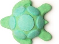 A green turtle shaped bath bomb that has some dark green patches on it's Shell, on a white background.