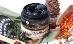 A short cylindrical black plastic tub with a black label that has northern soap for deep facial cleansing written in bright orange writing on it in front of some different coloured leaves and pinecones, on a white background.