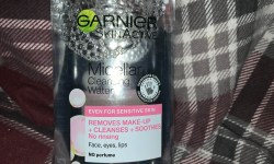 A tall rounded rectangular clear plastic bottle with a pink lid that has Garnier micellar Cleansing water written in bold black writing on it, on a white background.