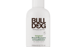 A tall cylindrical White Plastic Bottle that has bulldog skincare written in bold black writing and Original Beard Shampoo & Conditioner written in bright green writing on it, on a white background.