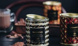 A short cylindrical silver metal tin with black stripes and a black label that has Whittard of Chelsea Marzipan Hot Chocolate written in bold gold writing on it, on a white background.