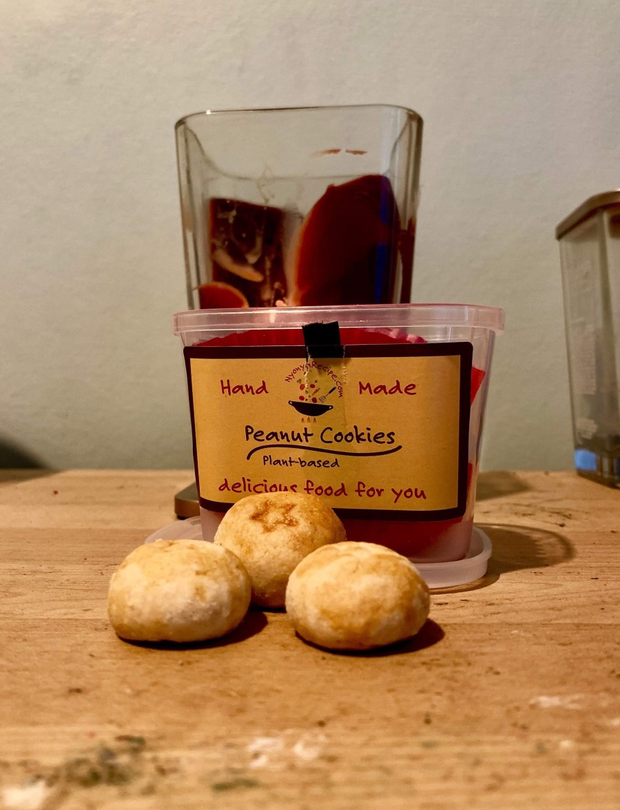 Some small circular light golden brown cookies with some pieces of Peanut embedded into them in front of a short rectangular clear Plastic Tub with a yellow label that has Nyonya Recipe Shop Peanut Cookies written in bold red writing on it on a light wooden table, on a white background.