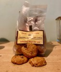 Some small circular light golden brown cookies that have some Chocolate Chips embedded in them in front of a large rectangular clear Plastic Bag with a yellow label that has nyonya recipe shop chocolate chip & nut cookies written in bold red writing on it on a light wooden table, on a white background.