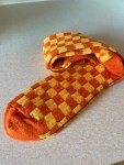 A pair of large orange and yellow checked socks, on a white background.
