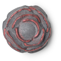 A large black rose shaped bath bomb that has a bright pink centre, on a white background.