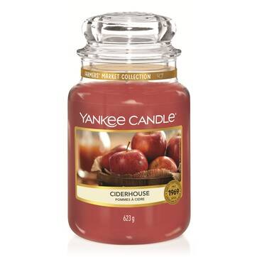 A tall glass jar full of some bright red wax with a label that has Yankee Candle written in white writing, Ciderhouse written in black writing , and some pictures of some Apples on it, on a white background.