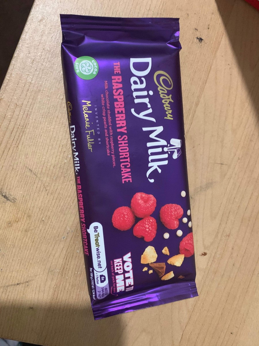 A tall rectangular purple chocolate bar that has Cadbury Dairy Milk written in bold white writing, The Raspberry Shortcake written in bold pink writing, and a picture of some plump raspberries on it, on a white background.