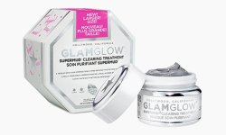 A short cylindrical white Glass Jar with a white lid that has GlamGlow SuperMud® Clearing Treatment written in bold silver writing and a picture of a silver star on it next to a bright white octagonal shaped cardboard box that has GlamGlow written in bold black writing and SuperMud® Clearing Treatment written in bold black writing on it, on a white background.