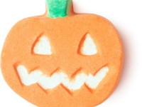 A small flat jack-o-lantern shaped bath bomb that has a white carved Face embedded on it, on a white background.