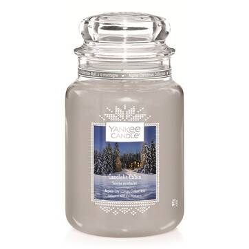 A tall glass jar full of some ice blue wax with a label that has Yankee Candle written in black writing, Candlelit Cabin written in white writing, and a picture of a large brown log cabin on it, on a white background.