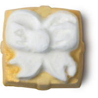 A large square shimmering gold wrapped present shaped bath bomb covered in some gold lustre, on a white background.