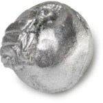 A large bright green Apple shaped block of soap that's covered in some bright silver lustre with a dark brown stem and a cut in the middle of it that's filled with some bright white cocoa butter, on a white background.
