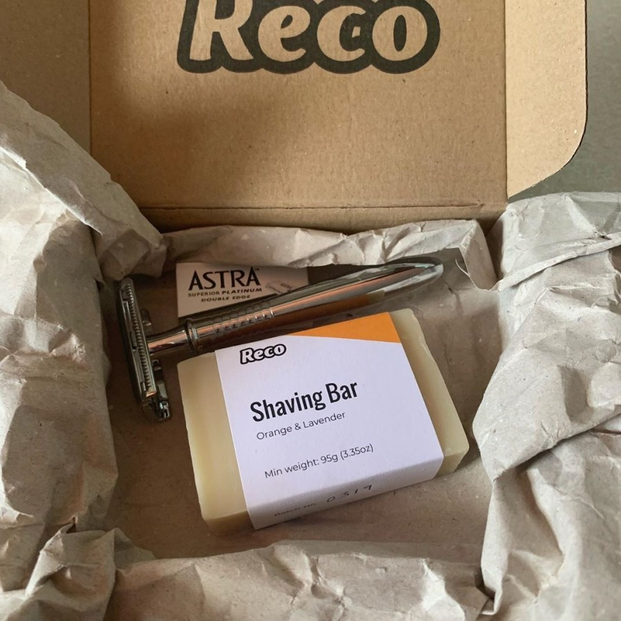 A long and thin cylindrical silver metal razor handle next to a small rectangular cardboard box that has Reco written in bold black writing on it and a large rectangular block of white soap with a rectangular paper wrapper that has orange and lavender shaving soap written in bold black writing on it, on a white background.