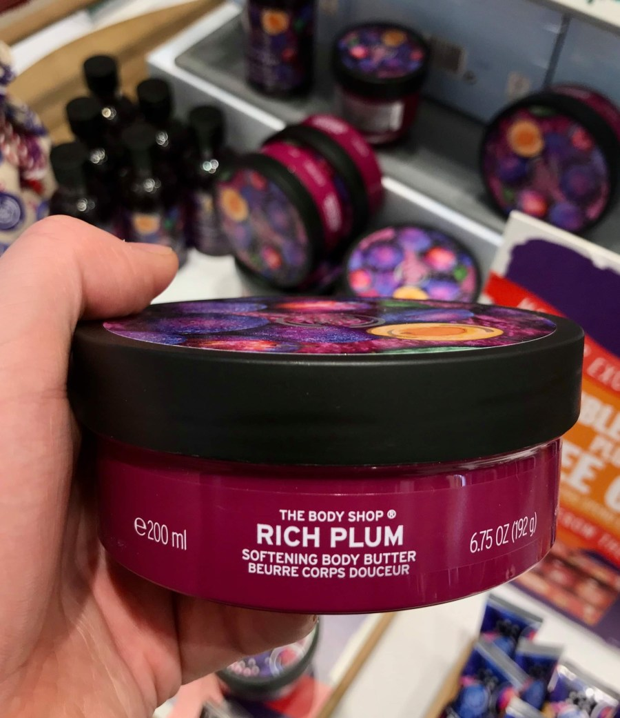A large circular dark purple plastic Tub with a white plastic lid and a bright red label that has the body shop rich plum body butter written in bold white writing and some pictures of some plums on it, on a white background.