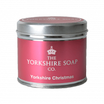 A short cylindrical silver tin with a black label that has The Yorkshire Soap Company Yorkshire Christmas Tin Candle written in bold white writing on it, on a white background.