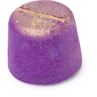 A large dark purple trapeze shaped bath bomb that's covered in some gold lustre and has a Cinnamon Stick sticking out of the top of it, on a white background.