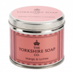 A short cylindrical silver tin with a bright pink label that has The Yorkshire Soap Company Mango & Lychee Tin Candle written in bold black writing and a picture of an orange crown on it, on a white background.
