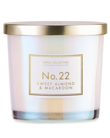 A medium cylindrical clear glass jar full of some bright white wax with a shiny gold metal lid and a white label that has Aldi Hotel Collection Sweet Almond & Macaroon Candle written in bold gold writing on it, on a white background.