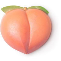 A large circular bright pink Peach shaped block of soap with a green stork coming out of the top of it, on a white background.