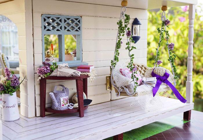 casuta din lemn detaliu de pe veranda cu balansoar