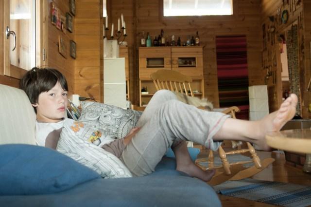 Tomi, Mon neveu autiste - enfant autiste -Photographie d'un garcon dans ses pensées assis dans un canapé. © Lumi Poullaouec