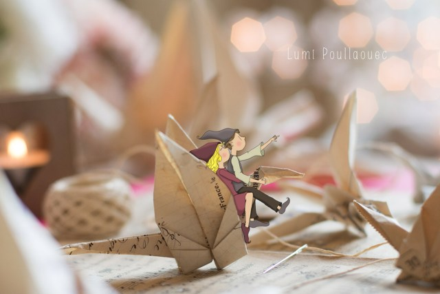 Photo d'une grue origami dans des couleurs douces avec du bokeh? Un couple amoureux de lutins y sont accrochés comme pour s'envoler vers leurs rêves.