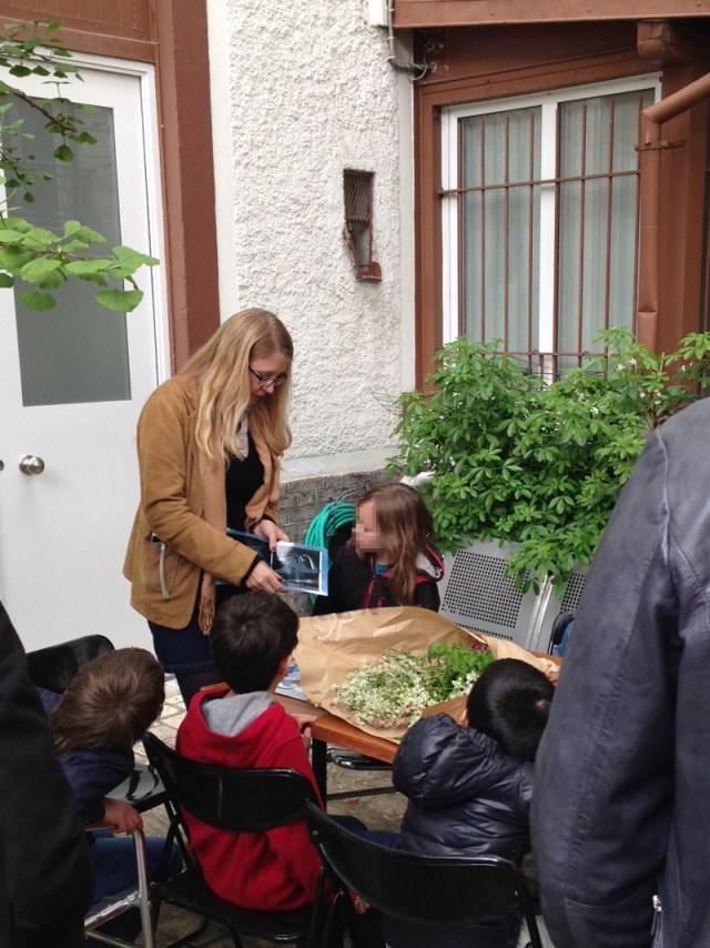 Lumi Poullaouec montrant des cyanotypes aux enfants lors de l'atelier.