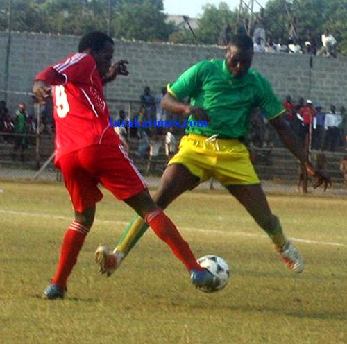 Nkana striker Maxwell Phiri dribbles hard working Prison Leopards defender Reginald Katila in a Division One North league match at Nkana stadium.