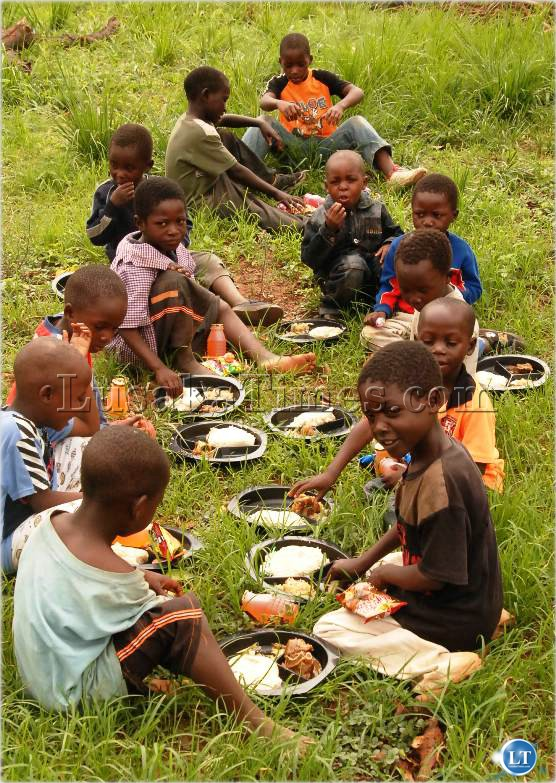 ENJOYING A HEARTY MEAL - NYAMPHANDE ORPHANAGE CHILDREN HAVING THEIR EARLY CHRISTMAS MEAL