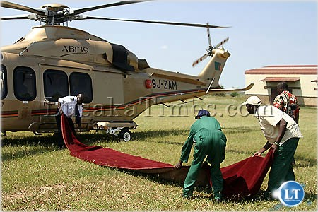 A Zambia Air Force flight assistant helps floor managers to lay a red carpet for President Banda in Mazabuka.