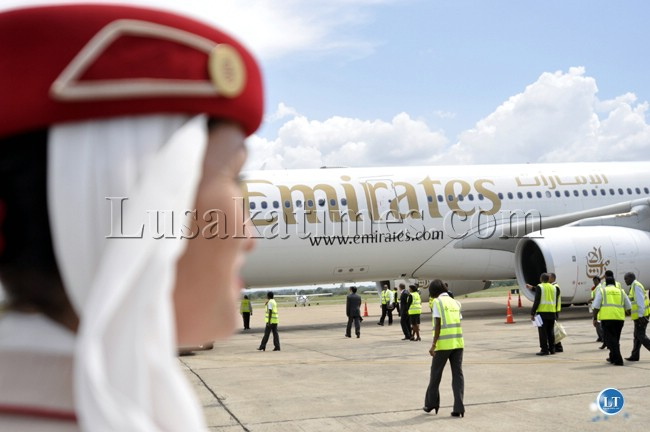 A member of the Emirates cabin crew watches plane  ground handling personnel attend to the airline's first direct flight from Dubai to Lusaka